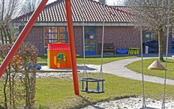 A playground with a swing and a playhouse: